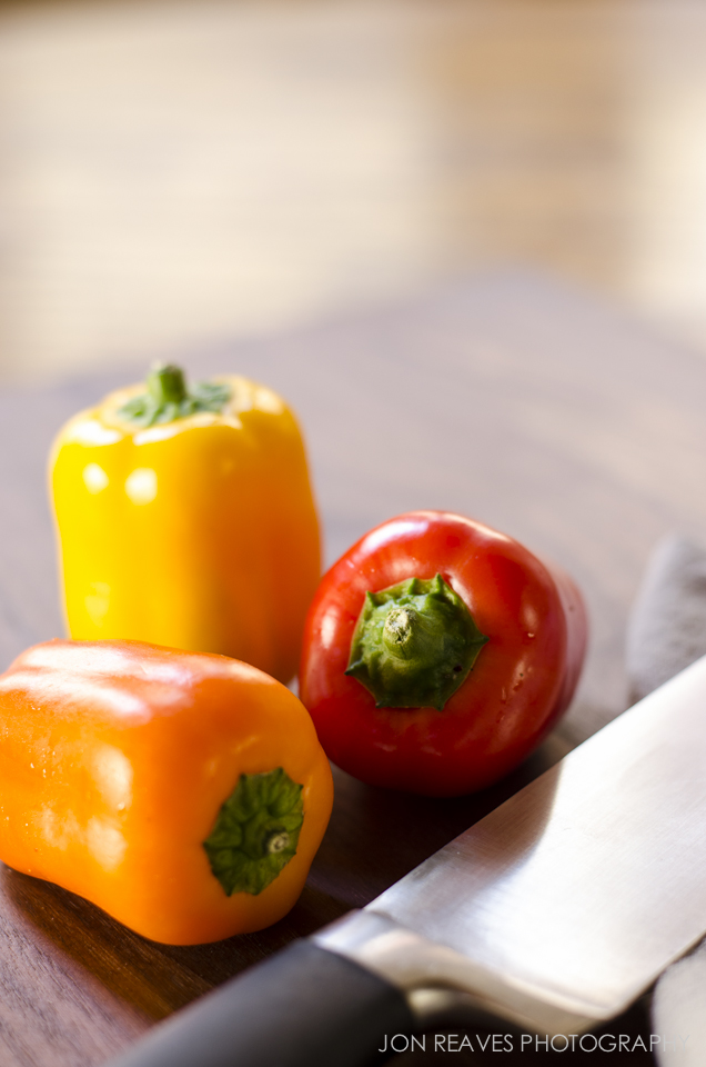 Colorful peppers and chef knife. The negative space provides room for clients to add text.