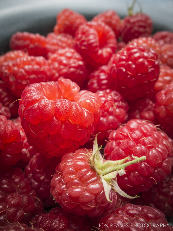 Freshly picked raspberries from my garden. I shot this outside on a sunny July day using the macro setting on a Fujifilm X10 point and shoot.