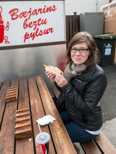 Alison (embarrassed) about to enjoy one of Iceland's famous (and cheap) hotdogs, 2015. Finding cheap eats is essential for budget travel.