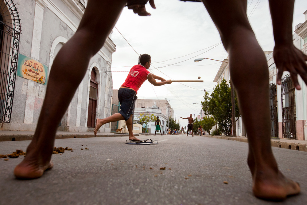 On 3-versus-3 teams, children play baseball, Cuba's most popular sport, on the streets of Cienfuegos. When a player hits the ball over a house and into its courtyard, it is considered a homerun. Many youngsters emulate their heroes in America's Major League Baseball and practice daily with the hopes of one day joining them.