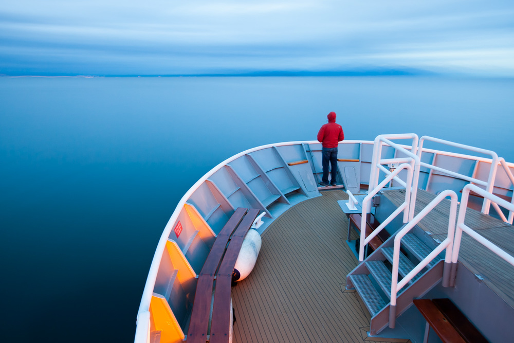 Aboard the National Geographic Sea Lion, a solo passenger looks towards the horizon while cruising through Alaska's Inside Passage.