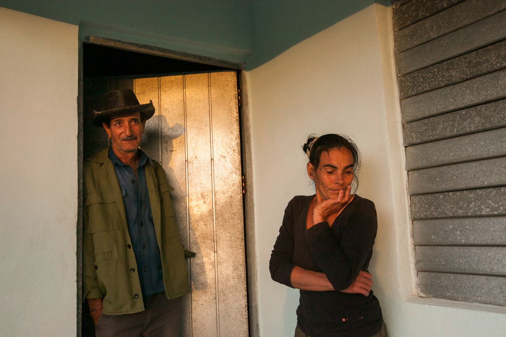 In Cienfuegos, Cuba, a woman and man stand in the doorway of their home.