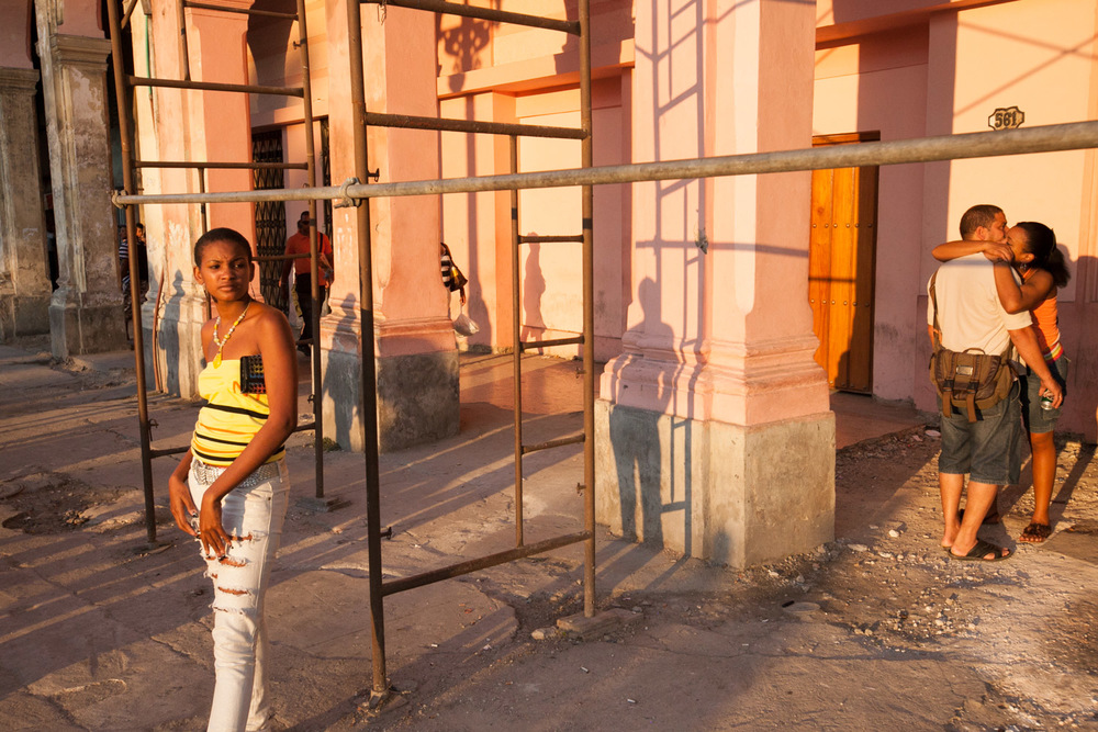 Locals and lovers pass the time at a bus stop in the heart of Havana.