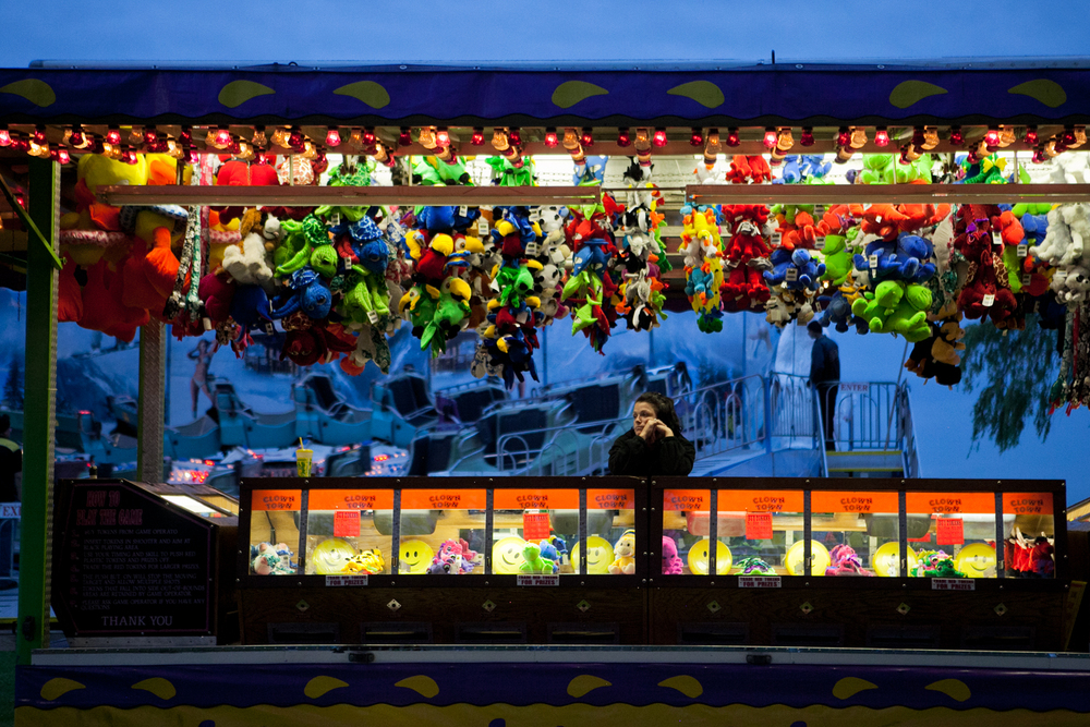 At each carnival location, workers are usually assigned to a specific ride, food stall, or game for the week's duration. As night falls, a carnival worker waits for visitors to play her game. When the carnival is open, workers usually attend to rides or games from noon until midnight.