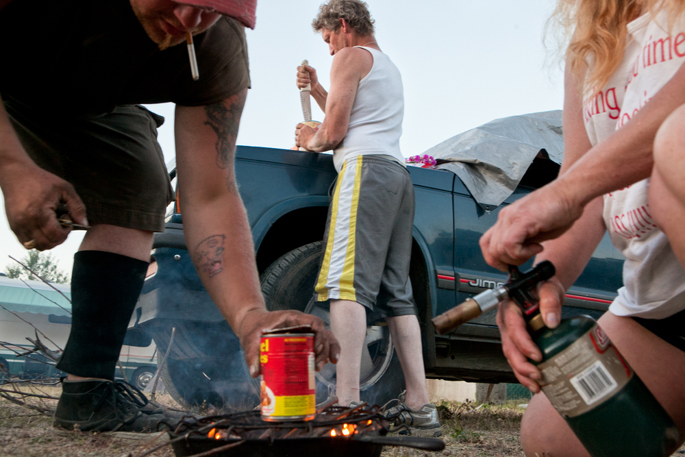 "This is a typical ""carny cookout."" Oftentimes carnival workers are living out of their cars and trucks while moving from one location to the next. Therefore, they usually purchase non-perishable foods. Two workers attend to a can of food on the grill, while a third worker opens another can with a knife."