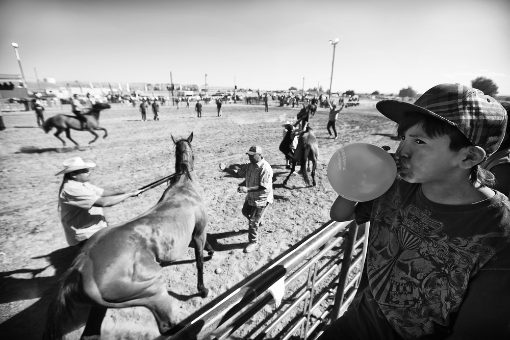 Indian Relay Races are staples at tribal rodeos and allow participants to acknowledge and revere their cultural history of horsemanship and bravery. A young Native American boy concentrates on his balloon as others participate in the Relay Races at the reservation's annual powwow and rodeo.