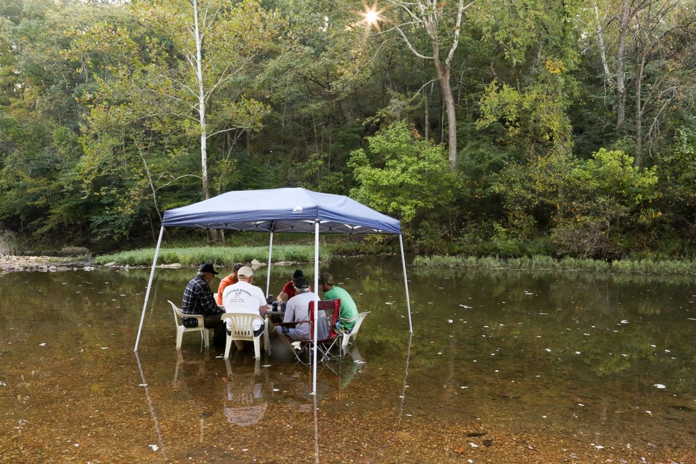 In a shallow creek on their farm, Paul and Joe join a group of friends and co-workers. During warmer months, they set up a table and canopy in the water to play cards and keep cool.