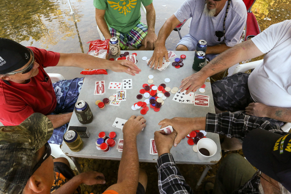 Paul and Joe play poker and drink beer with friends and coworkers. Their unique tradition started several years ago while camping during summer heat.