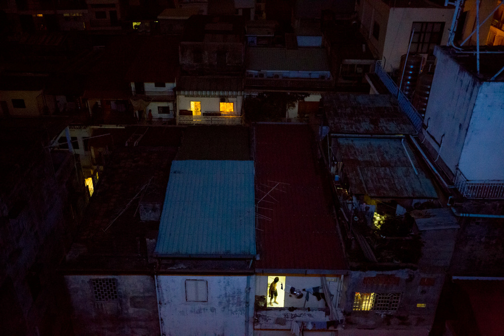 In Phnom Pehn, Cambodia, a man stands in a lit doorway among densely populated housing area.