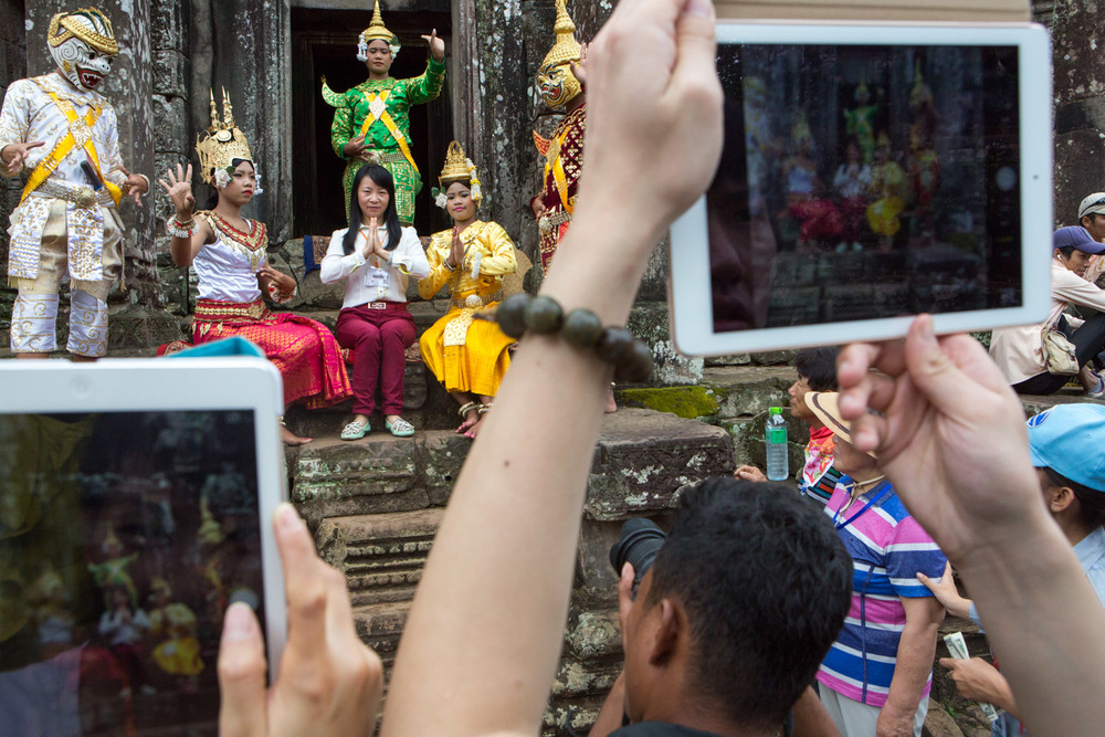 A visitor to the Angkor Thom complex in Cambodia has her picture made with a group of boys and girls who are in traditional costume. Several other visitors wait nearby for their opportunity. The boys and girls dress in costume and make a living by standing in the Angkor complex and posing for pictures with tourists.