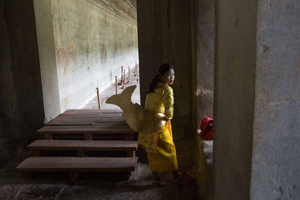 A young girl dons a costume inside the Angkor Wat Temple in Cambodia. She dresses in costume to pose for photos with visitors.