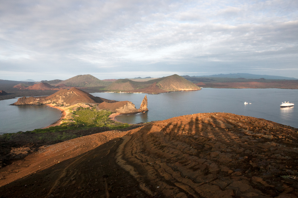 In the Galapagos Islands, the shadows of tourists are visible on the backdrop and landscape of Bartolome Island. An expedition vessels anchors in the water.