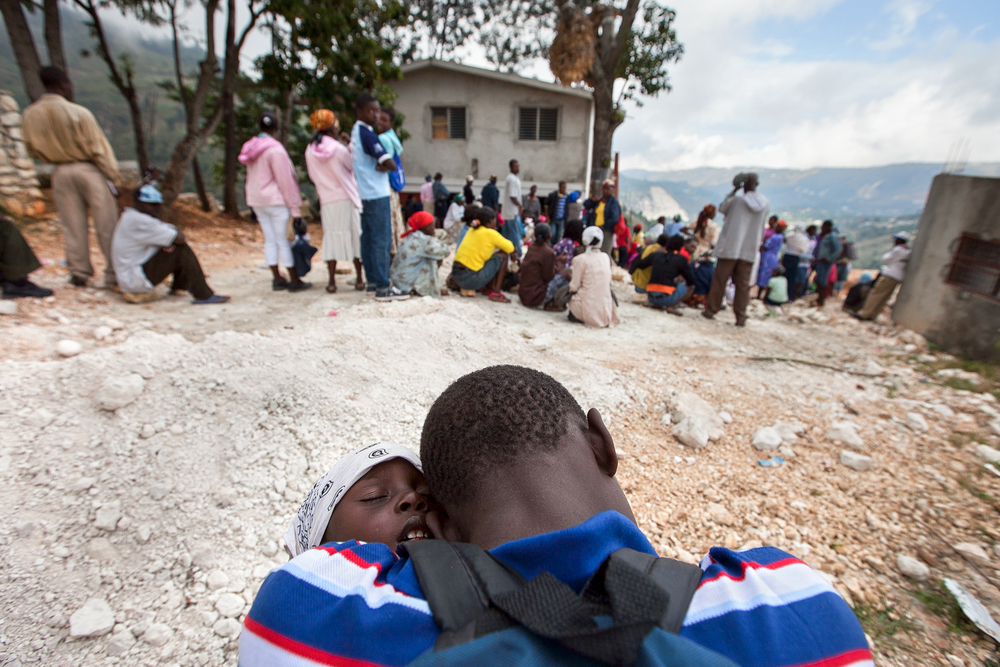Two boys sleep on one another as they await their turn with a nurse at Gramothe's medical clinic. The teen carried his younger sibling for hours on foot to seek treatment. Medical teams from outside Haiti provide care to villagers several times a year.