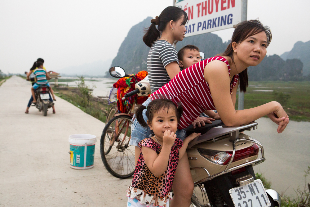 At Van Long, in Vietnam's Ninh Binh province, a family gathers on their motorbike and observes the rugged landscape.
