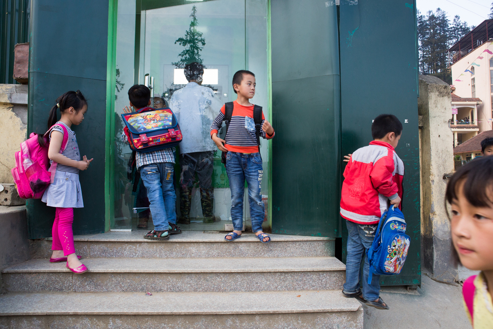 In Sapa, Vietnam, children from a nearby school gather around an automated banking machine.