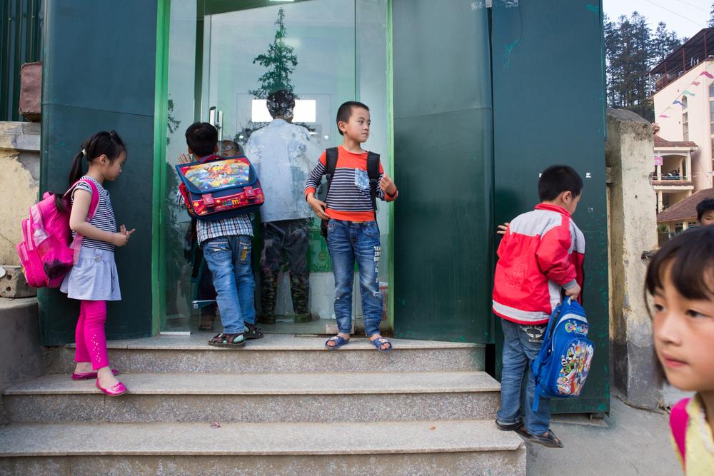 In Sapa, Vietnam, children from a nearby school gather around an automated banking machine.