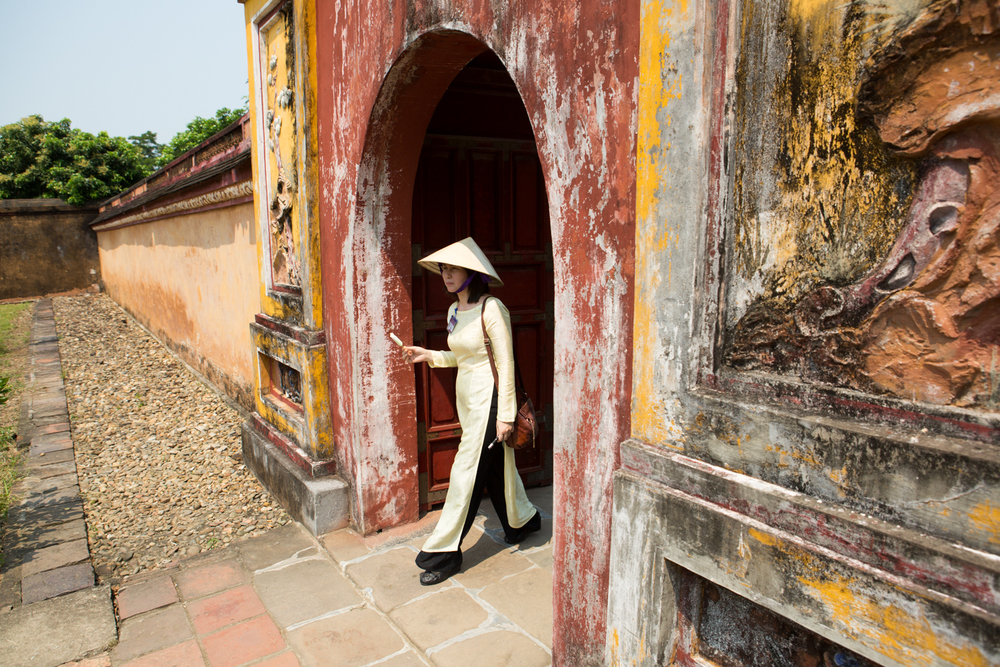 A Vietnamese tour guide eats ice cream as she walks through The Citadel - The Royal Palace - in Hue, Vietnam.