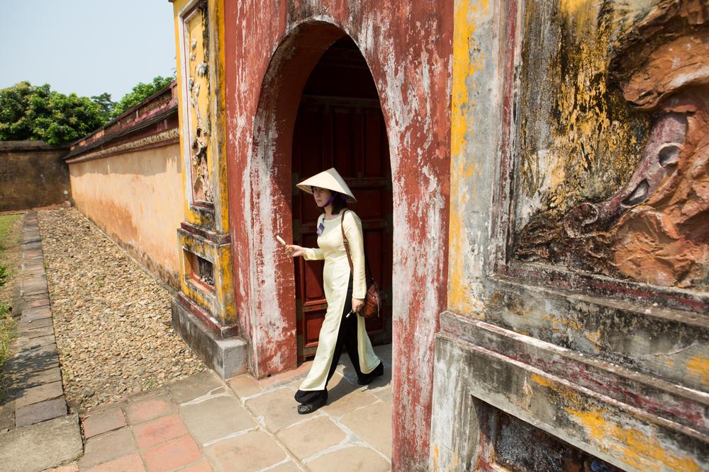 A Vietnamese tour guide eats ice cream as she walks through The Citadel - The Royal Palace - in Hue, Vietnam.