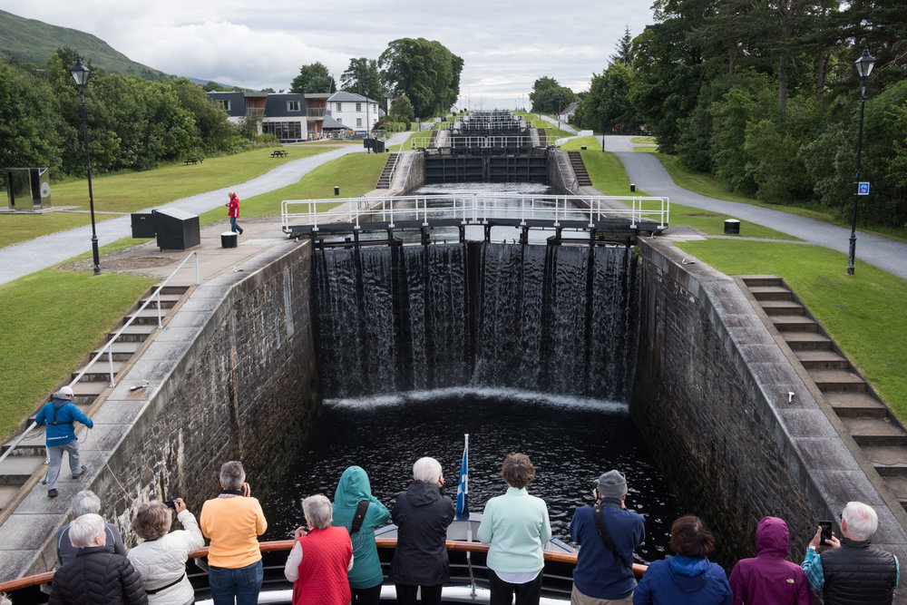 Guests gather on the bow of the ship to watch it ascend Neptune's Staircase, a sequence of eight locks along the Caledonian Canal.