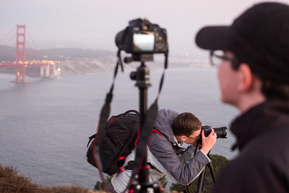 At dusk, two students photograph at The Golden Gate Bridge Vista Point.