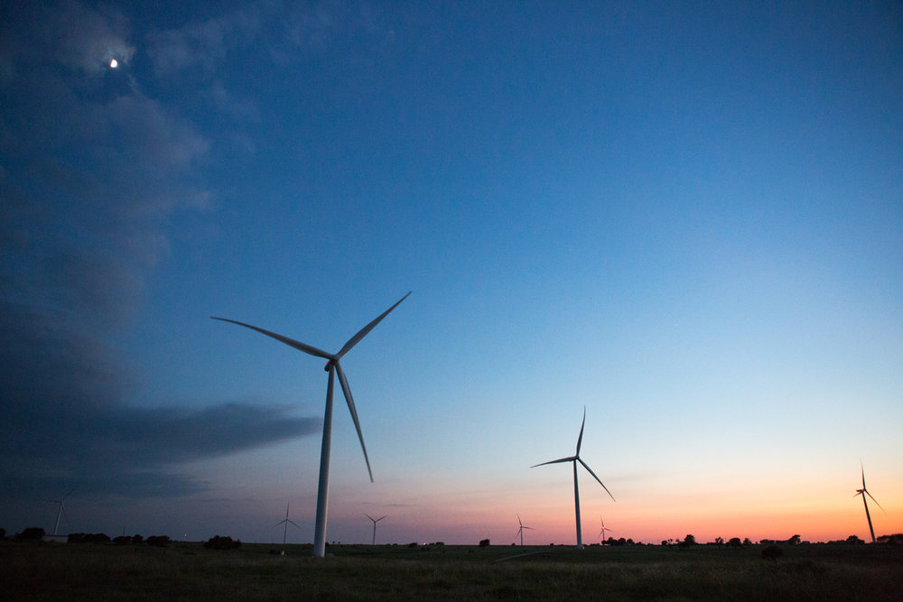 At dusk under moonlight, several wind turbines fill the landscape at Tyler Bluff Wind Facility in Muenster, Texas.