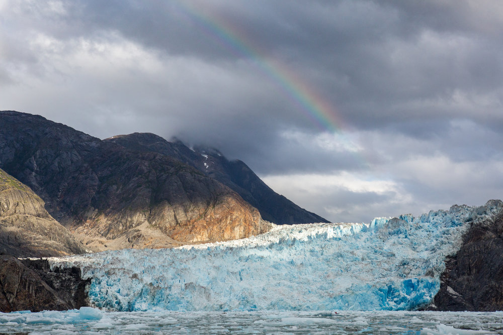 A rainbow stretches over the face of Sawyer Glacier, in Tracy Arm, Alaska.
