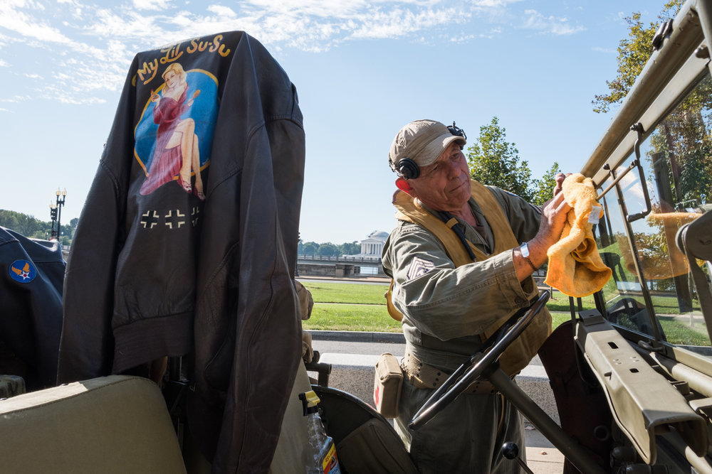 Joe Becker, a war re-enactor with the Allied Airmen's Preservation Society, cleans the Willy Jeep windshield near the World War II Memorial in Washington, D.C. during an Honor Flight event. Honor Flight is when veterans from around America visit the memorials on The National Mall.