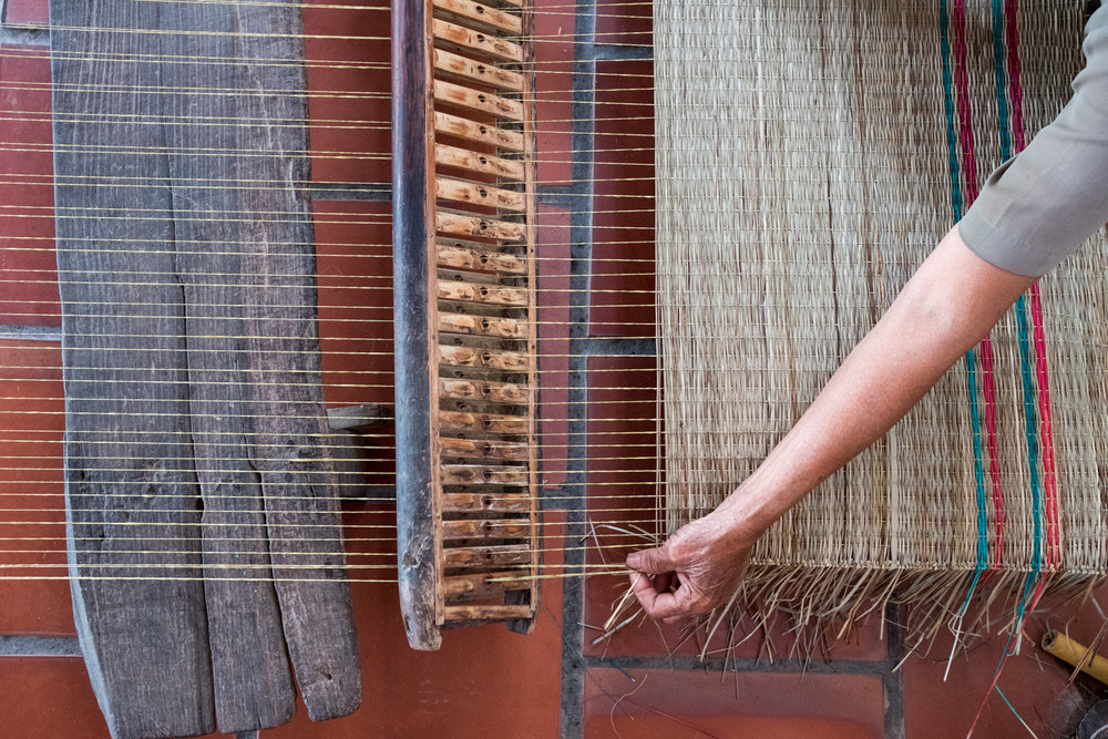 On Binh Thanh Island, a local woman works on a rattan mat.