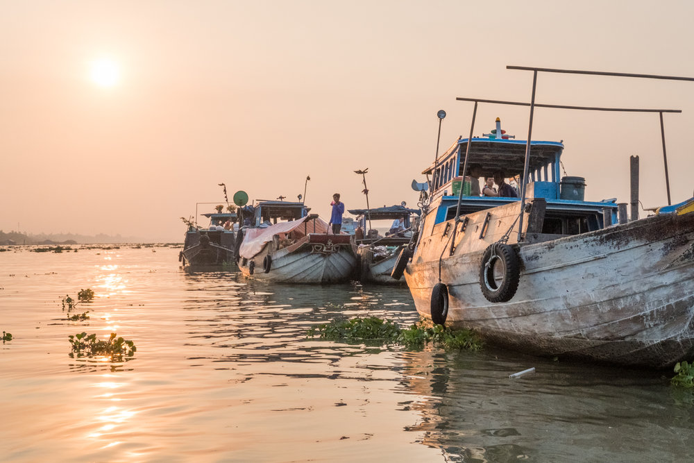 In Chau Doc, Vietnam, boats line up at sunrise to prepare for selling goods at the floating market.