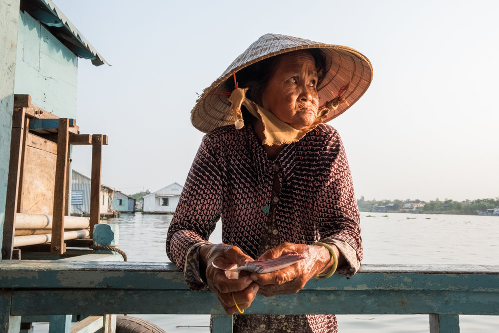 Chau Doc, Vietnam is one of the best places to see villages comprised of floating houses and fish farms. While visiting one of the houses, this woman approached in her boat and asked if I'd like to buy lottery tickets.