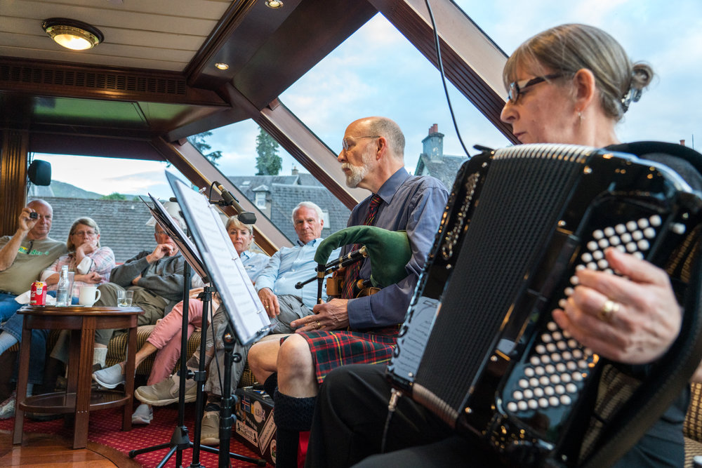 Aboard Lord of the Glens at Fort Augustus, Scotland, local musicians entertain guests with traditional instruments.