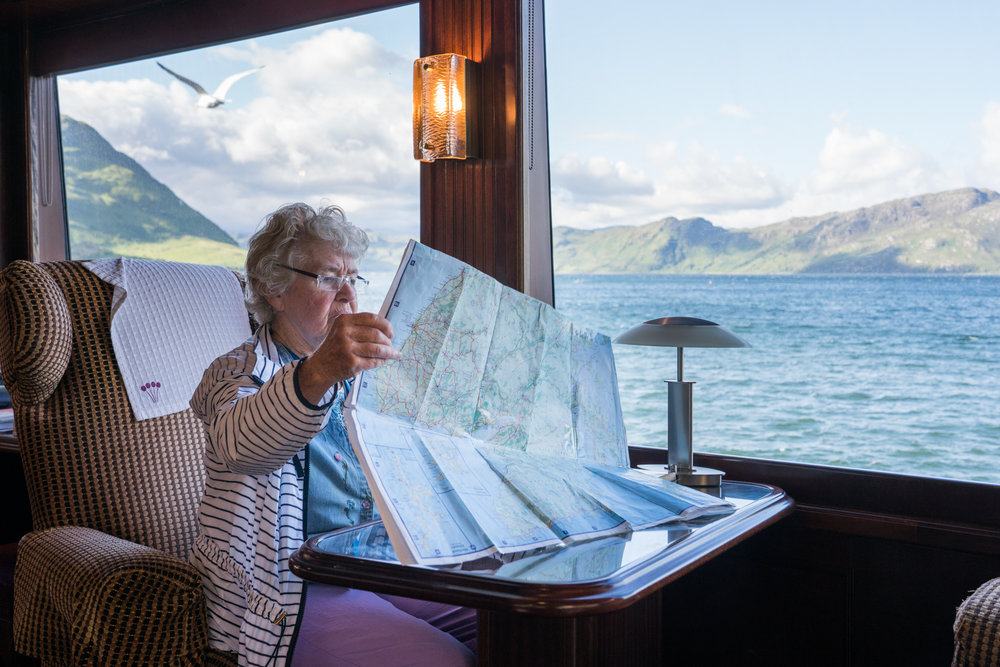 Outside Armadale, Scotland, a guest studies a map aboard Lord of the Glens.