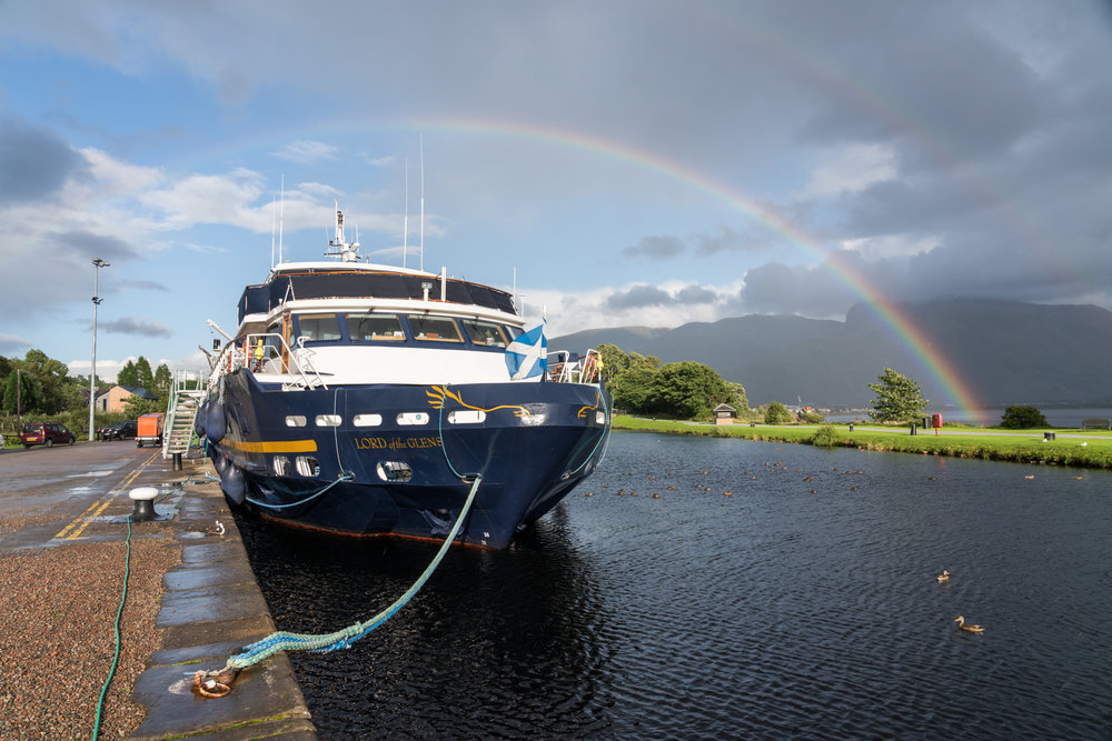 While docked in Corpach, Scotland, along the Caledonian Canal, a rainbow spans the landscape.