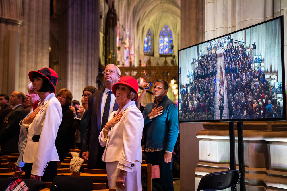 Attendees stand and acknowledge The National Anthem as the final procession passes through the cathedral.