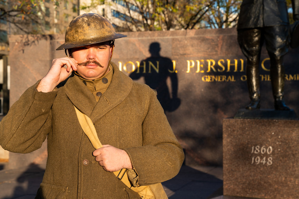 A World War I American troop re-enactor twirls his mustache in Pershing Park.