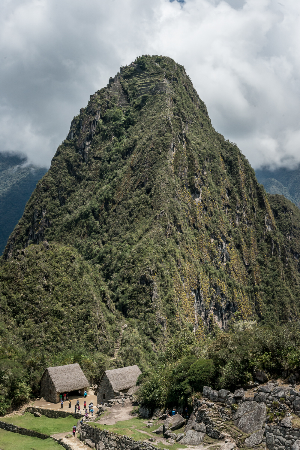 A closer view of Hayna Picchu. We can see the beginning of the path just behind the two huts, but then the path disappears and can only be seen again near the top.