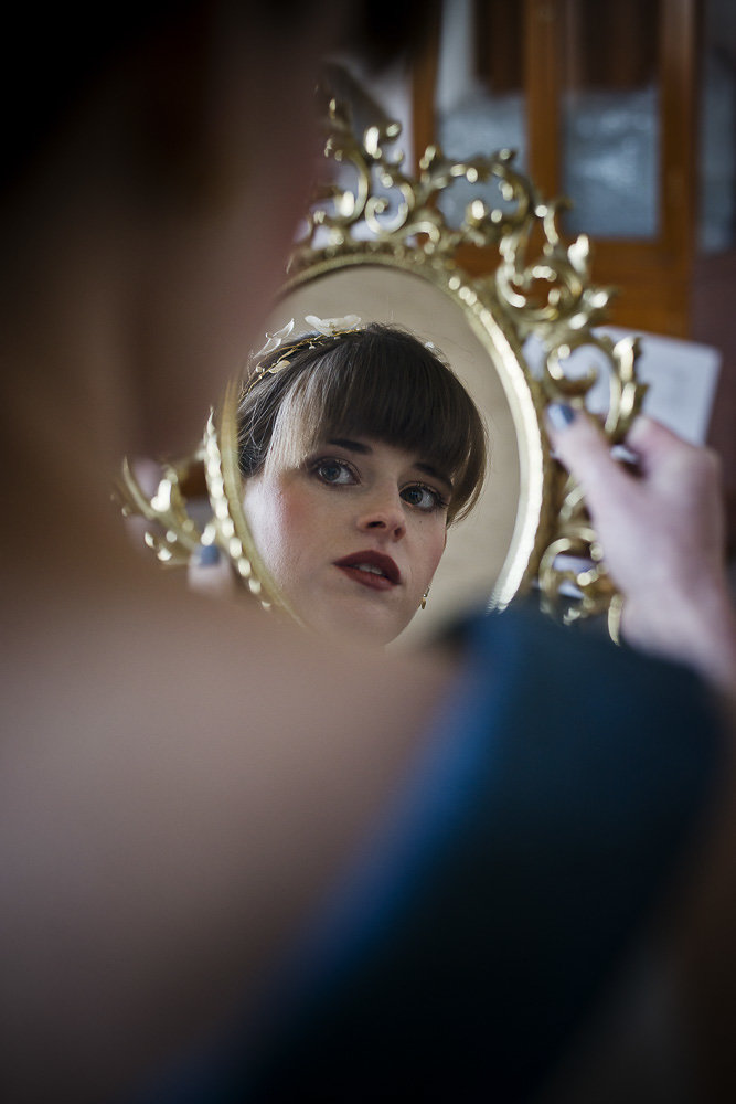 bride looking in gold mirror getting ready on wedding day wedding photography