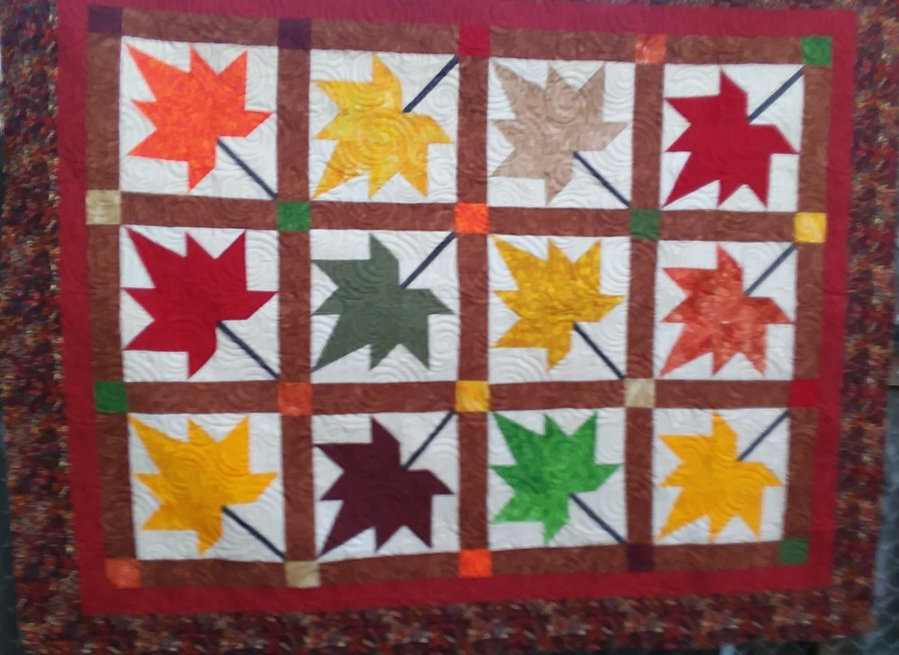 Autumn Leaves Quilt - The lovely twelve block leaf pattern is done in autumn hues of red, yellow, orange, green and brown. It is designed to fit a double bed.