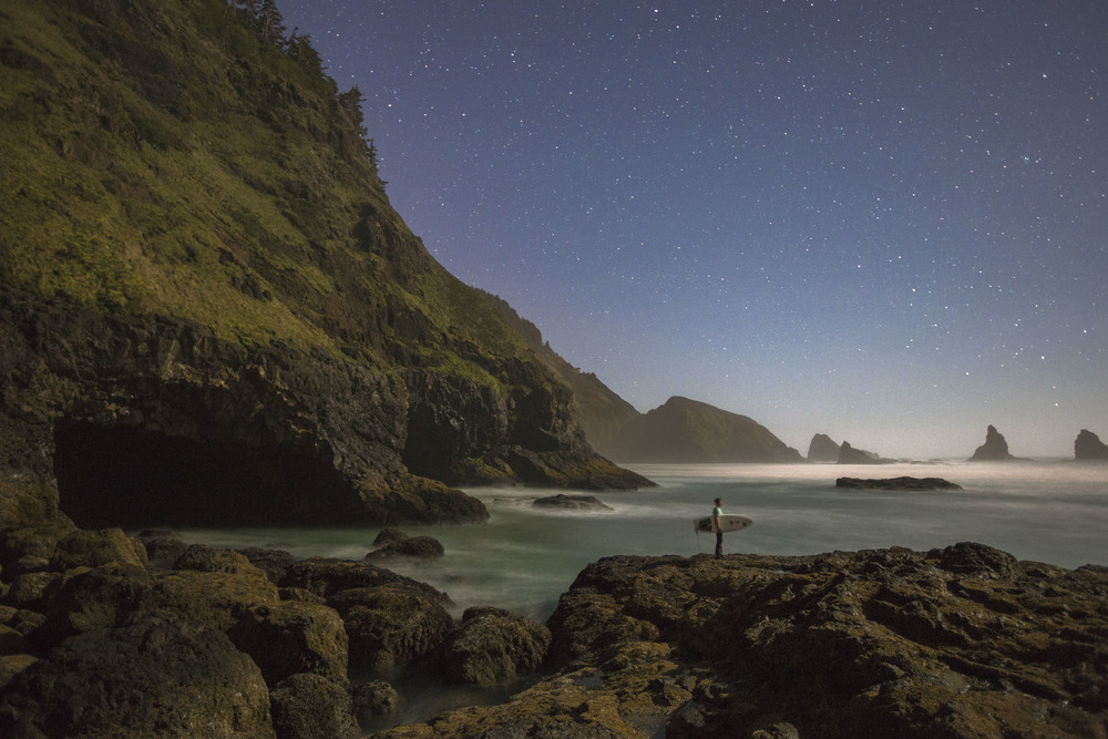 """Field Notes    Photo by Jarrett Juarez   Location: Near Cape Meares, Oregon    Inspired by the clear sky and full moon, photographer Jarrett Juarez threw his camera gear and surf boards into his van to see what he could create. At around 11:30 PM, he arrived at the coast and began searching for the photo he envisioned—making his way around sea caves and over tidepools to set up the shot.     """"The spot I wanted to be was 50 yards from the camera and I had 10 seconds to run across sharp volcanic rock with only the light from the moon and a $10 Walmart headlamp to guide me into position. I ended up shooting for an hour and after about 20 shots, a boot full of sea water and a smidge of hypothermia from the December air—I ended up with this one.""""    Camera: Canon EOS 5D Mark III   Lens: EF16-35mm f/2.8L II USM   Focal Length: 23.0 mm   Shutter speed: 20.0 sec    Aperture: f/2.8  ISO: 2500"""