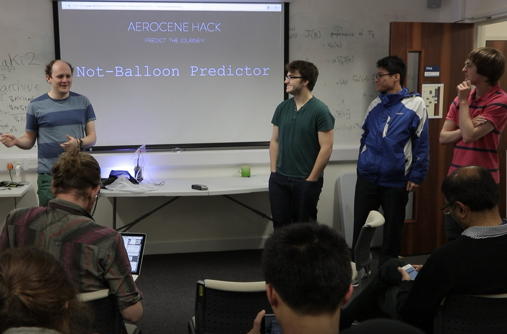 "Adam, Jamie, Yun, and Daniel of the ""Not-Balloon Predictor"" team giving their final presentation at the end of the Hack."