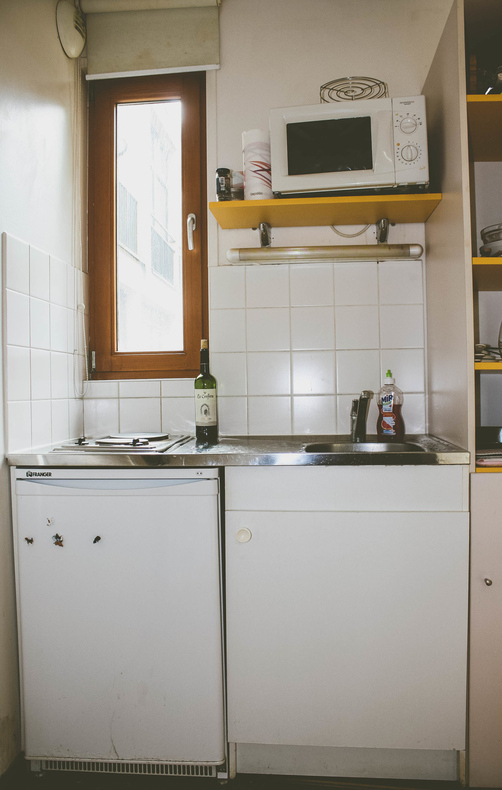 First Apartment in Paris: a kitchen including a tiny little refrigerator and two electric hot plates.