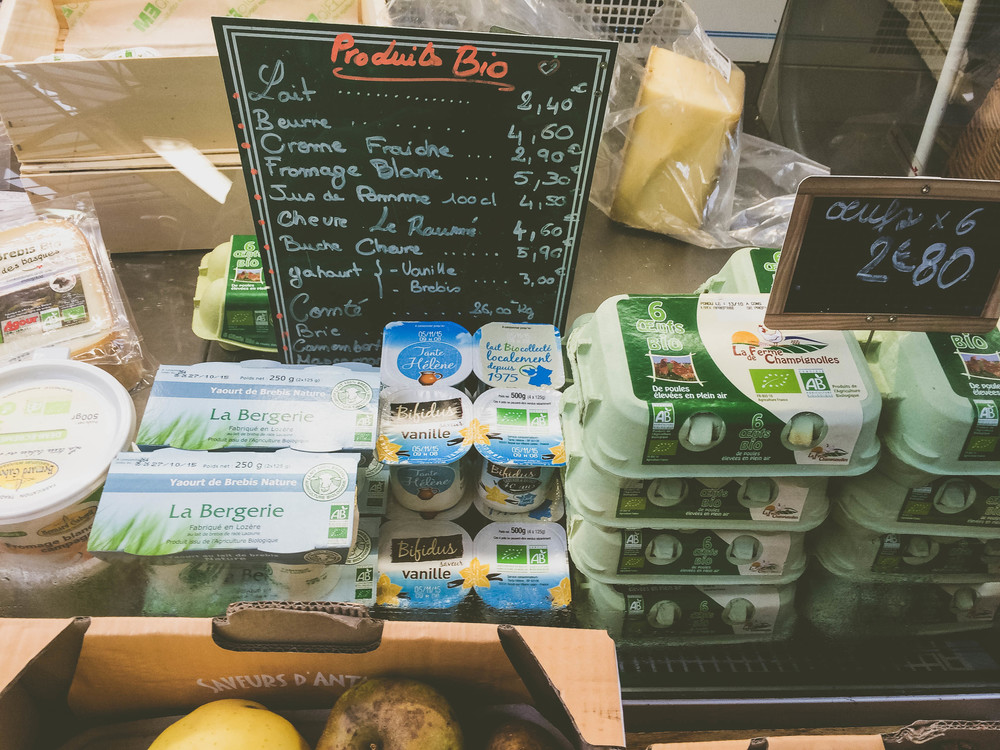 organic dairy products all lined up in a chilled case at the market.