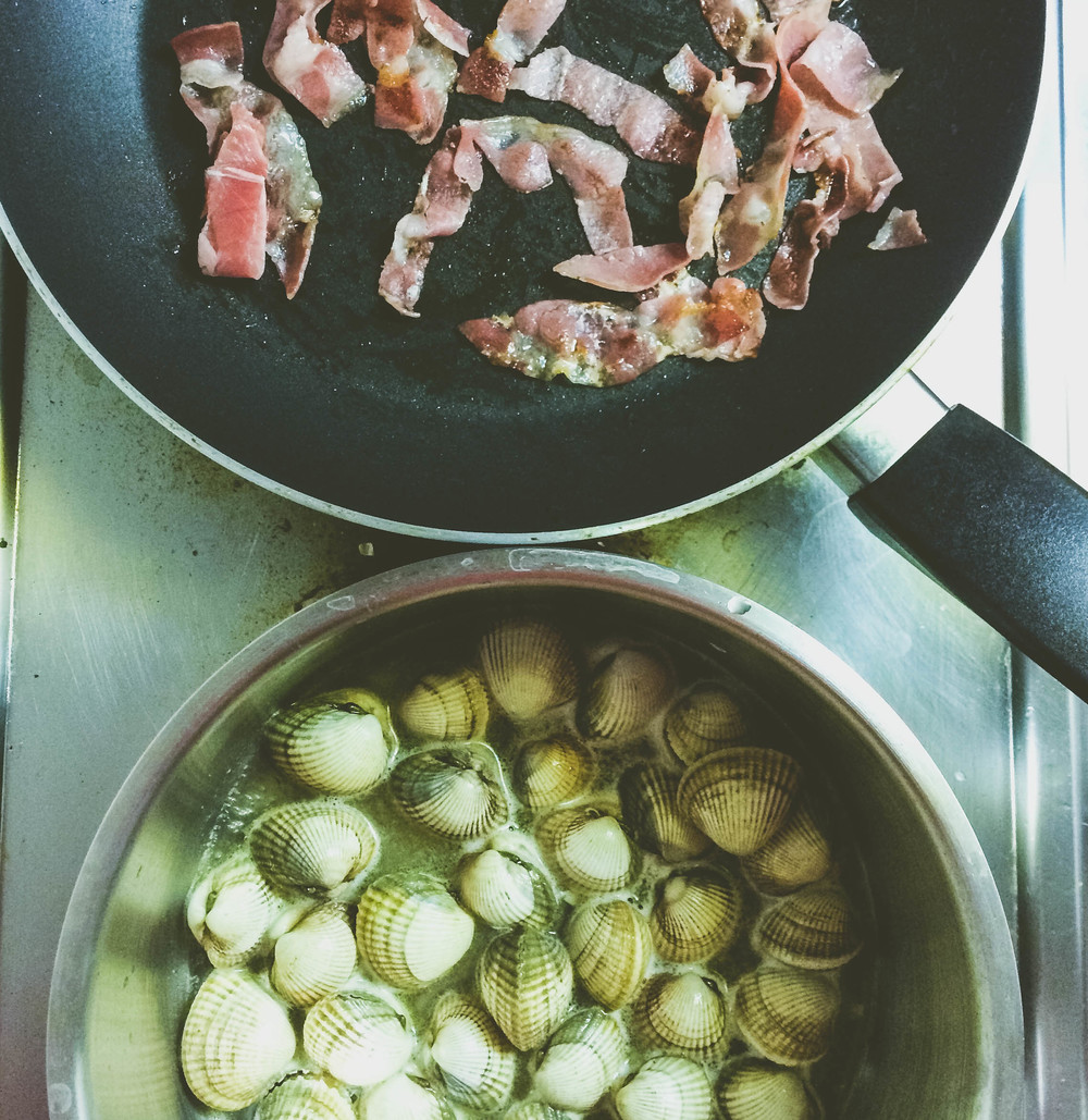 Cockles and Pancetta cooking for a pasta dish