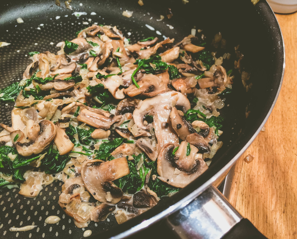 Mushrooms, onions and spinach cooking together