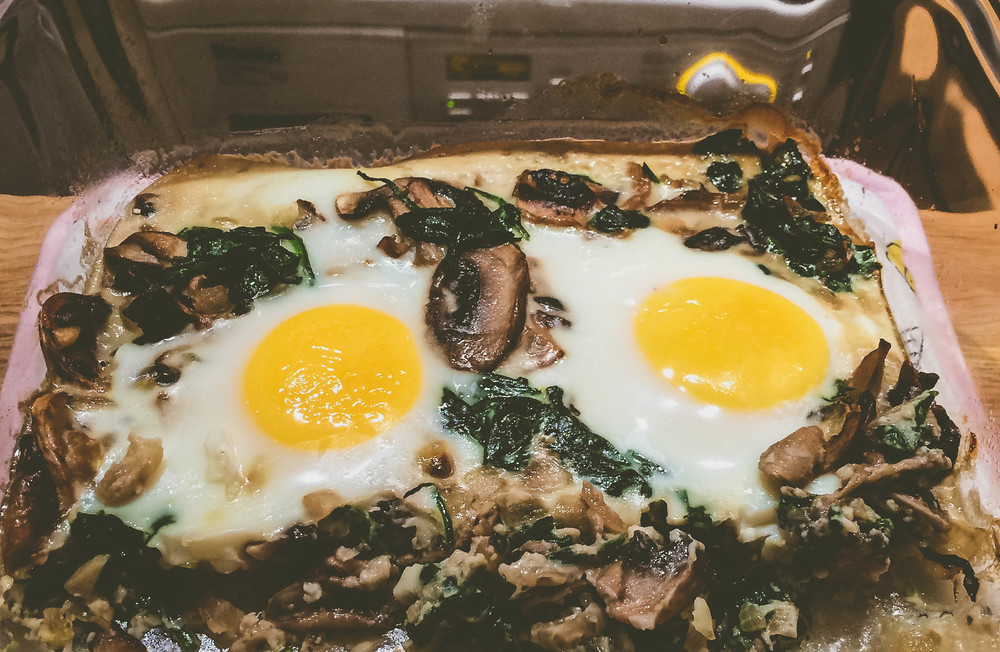 One portion of baked eggs with spinach and mushrooms. Look at those bright yellow yolks!