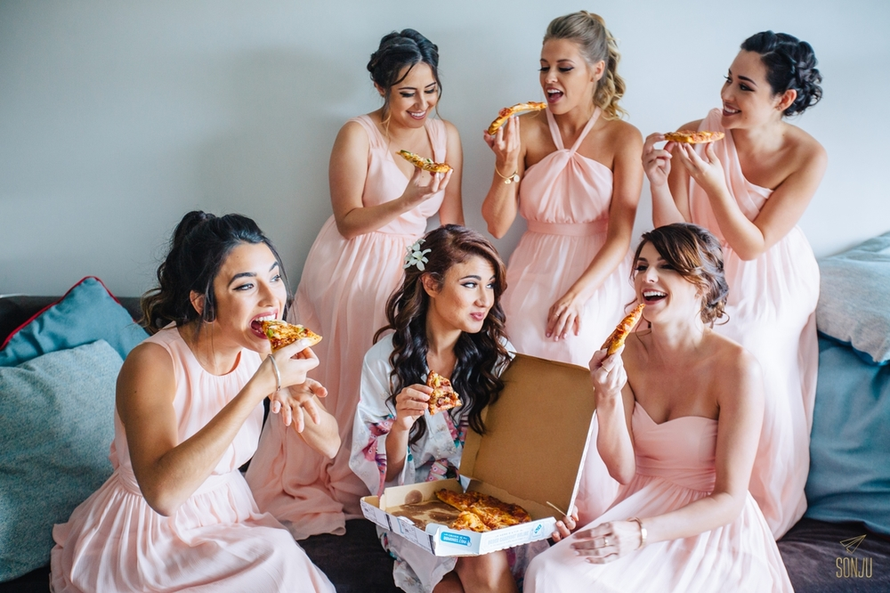Bride and bridesmaids eating pizza