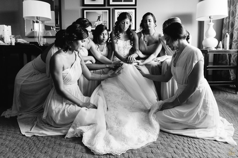 Bride prays with bridesmaids