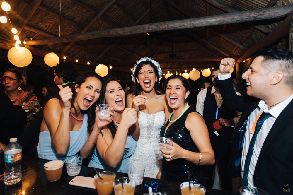 Bride taking shots at bar with bridesmaids