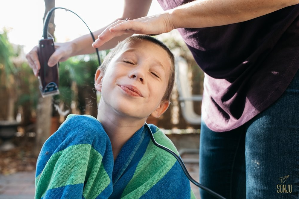 boy getting haircut by mom outside on patio
