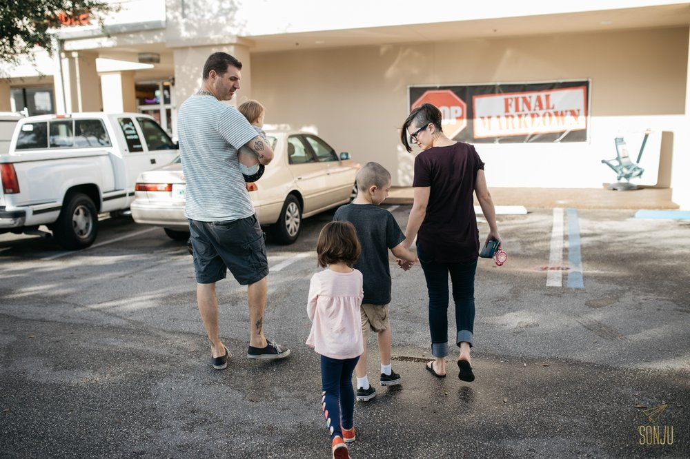 family walking in parking lot with children